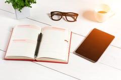 Bureau de table de bureau avec l'ensemble d'approvisionnements, bloc-notes vide blanc, tasse, stylo, comprimé, verres, fleur sur  Image libre de droits