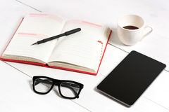 Bureau de table de bureau avec l'ensemble d'approvisionnements, bloc-notes vide blanc, tasse, stylo, comprimé, verres sur le fond Image libre de droits