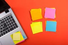 Bureau de table de bureau avec l'ensemble d'approvisionnements, d'ordinateur portable et de rappel colorés sur le fond rouge Vue  Image libre de droits