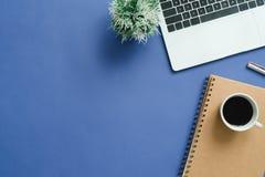 Bureau de vue supérieure avec l'ordinateur portable, les carnets et la tasse de café sur le fond bleu de couleur Image stock