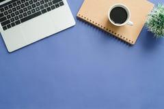 Bureau de vue supérieure avec l'ordinateur portable, les carnets et la tasse de café sur le fond bleu de couleur Photo stock
