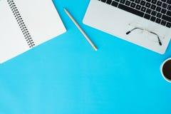 Bureau de vue supérieure avec l'ordinateur portable, les carnets et la tasse de café sur le fond bleu de couleur Photos libres de droits
