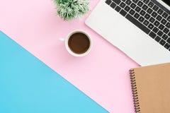 Bureau de vue supérieure avec l'ordinateur portable, les carnets et la tasse de café sur le fond de couleur en pastel Photo stock
