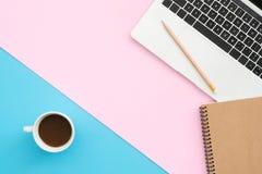 Bureau de vue supérieure avec l'ordinateur portable, les carnets et la tasse de café sur le fond de couleur en pastel Photos stock