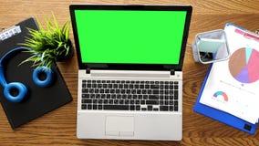 Bureau de vue supérieure avec un ordinateur portable avec l'écran de vert de chroma là-dessus à côté des presse-papiers clips vidéos
