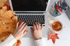 Bureau de vue supérieure Espace de travail avec les mains femelles, ordinateur portable, tasse de thé, agrafes d'or, verres Conce Photo stock