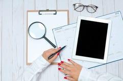 Bureau de vue supérieure Espace de travail avec les mains, le presse-papiers, le calendrier et le comprimé femelles Photo libre de droits