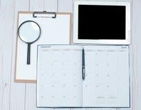 Bureau de vue supérieure Espace de travail avec les mains, le presse-papiers, le calendrier et le comprimé femelles Image stock