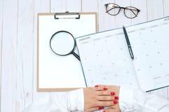 Bureau de vue supérieure Espace de travail avec les mains, le presse-papiers, le calendrier et la loupe femelles Photographie stock libre de droits