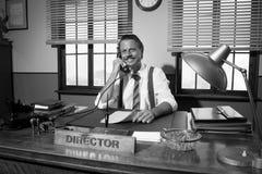 bureau des années 1950 : directeur travaillant au téléphone Images stock