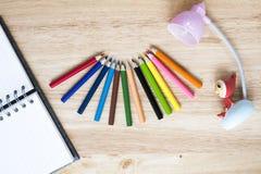 Bureau en arte kantoorbehoeftenvoorwerpen op houten lijst met een notitieboekje Stock Foto