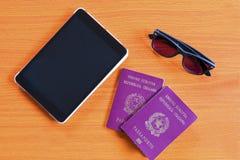 Bureau en bois avec des passeports de comprimé et des verres de soleil suggérant l'e photographie stock