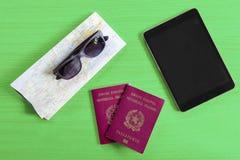 Bureau en bois avec des verres de soleil de passeports de comprimé et carte suggérant t image stock