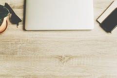Bureau en bois avec l'ordinateur portable, le téléphone, le carnet, les verres et l'usine Images libres de droits