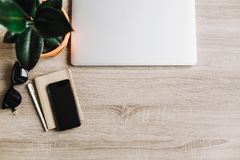 Bureau en bois avec l'ordinateur portable, le téléphone, le carnet, les verres et l'usine Image libre de droits