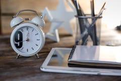 Bureau en bois conceptuel moderne ou table à la maison de bureau avec le comprimé, le carnet, la tasse de stylos et l'horloge de  Image stock