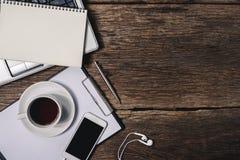 Bureau en bois de bureau avec le stylo, bloc-notes, tasse de café, smartphone et Photo libre de droits
