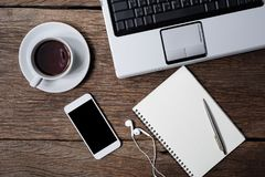 Bureau en bois de bureau avec le stylo, bloc-notes, tasse de café, smartphone et Images stock