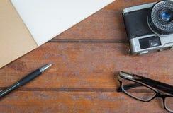Bureau en bois de créatif, concepteur avec le carnet, verres, stylo et appareil-photo Photo stock