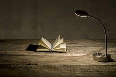 Bureau en bois rustique d'étude avec la lampe de table allumée et le carnet ouvert Images libres de droits