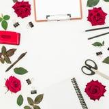 Bureau féminin d'espace de travail avec le presse-papiers, le carnet, les accessoires et les fleurs rouges sur le fond blanc Conf Images libres de droits