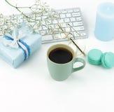 Bureau féminin de bureau, espace de travail avec l'ordinateur portable, tasse de café, macarons, cadeau et fleurs Photo stock