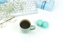 Bureau féminin de bureau, espace de travail avec l'ordinateur portable, tasse de café, macarons, cadeau et fleurs Photo libre de droits