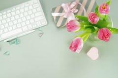 Bureau féminin, espace de travail avec un bouquet Photos stock