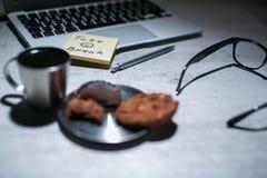 Bureau fonctionnant de bureau avec l'ordinateur portable, le stylo et et les verres et le café avec le biscuit et les autocollant Photo stock