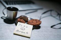 Bureau fonctionnant de bureau avec l'ordinateur portable, le stylo et et les verres et le café avec le biscuit et les autocollant Images stock