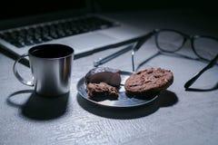 Bureau fonctionnant de bureau avec l'ordinateur portable, le stylo et et les verres et le café avec le biscuit et les bonbons Photos libres de droits
