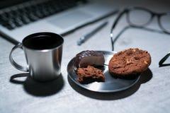 Bureau fonctionnant de bureau avec l'ordinateur portable, le stylo et et les verres et le café avec le biscuit et les bonbons Image stock
