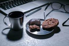 Bureau fonctionnant de bureau avec l'ordinateur portable, le stylo et et les verres et le café avec le biscuit et les bonbons Images stock