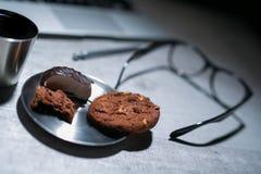 Bureau fonctionnant de bureau avec l'ordinateur portable, le stylo et et les verres et le café avec le biscuit et les bonbons Photos stock