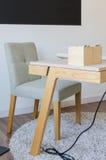 Bureau fonctionnant en bois moderne avec la chaise sur le tapis Photo stock