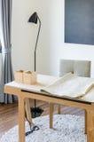 Bureau fonctionnant en bois moderne avec la lampe moderne et chaise sur le tapis Photographie stock libre de droits