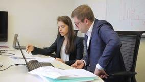 In bureau geeft de vrouw een verklaring aan de mens bij bureau met laptops stock videobeelden