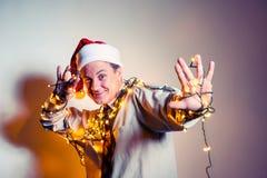 Bureau grappige mens in Santa Claus rood GLB met gele slingers Collectief gebeurtenissenconcept Stock Foto's