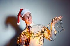 Bureau grappige mens in Santa Claus rood GLB met gele slingers Collectief gebeurtenissenconcept Stock Afbeelding