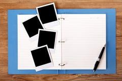 Bureau met blauwe projectomslag en lege foto's royalty-vrije stock afbeelding
