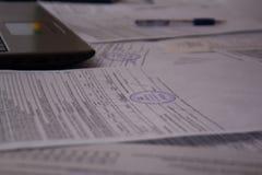 Bureau met documenten, ontvangstbewijzen en documenten Het werk met documenten bij de installatie of de onderneming Laptop of com stock foto