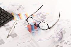 Bureau met grafieken, toetsenbord, glazen, pen en verscheurde documenten stock fotografie
