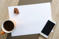 Bureau met Witboek, koffie, chocolade en telefoon op het Royalty-vrije Stock Foto's