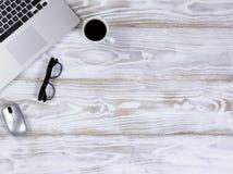 Bureau mobile sans fil fonctionnant sur le bureau en bois blanc rustique Image stock