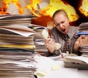 Bureau op brand en vliegende document bladen stock afbeeldingen