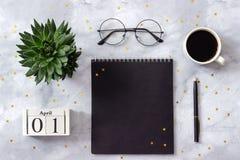 Bureau ou bureau à la maison de table Cubes calendrier bloc-notes en bois de noir du 1er avril, tasse de café, succulente, verres photo libre de droits