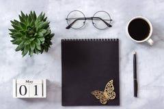 Bureau ou bureau à la maison de table Cubes calendrier bloc-notes en bois de noir du 1er mai, tasse de café, succulente, verres s images libres de droits