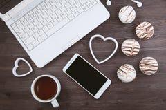Bureau plat de femme de configuration Espace de travail avec l'ordinateur portable, avec les gâteaux sensibles, deux coeurs sur l Image libre de droits