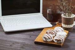 Bureau plat de femme de configuration Espace de travail avec l'ordinateur portable, avec les gâteaux sensibles, thé sur la table  Photo libre de droits