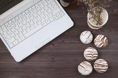 Bureau plat de femme de configuration Espace de travail avec l'ordinateur portable, avec les gâteaux sensibles, thé sur la table  Images stock